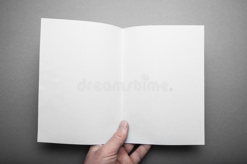 Manual start of white log with mockups of blank pages. A person reading two-page books looks at the first person royalty free stock photo