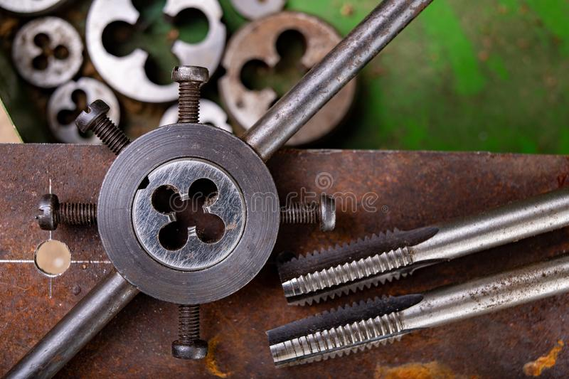 Manual thread cutting in metal. Locksmith accessories for small work in the home workshop. Dark background clamp construction die dies dirty engineering stock photo