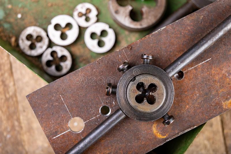 Manual thread cutting in metal. Locksmith accessories for small work in the home workshop. Dark background clamp construction die dies dirty engineering stock photos