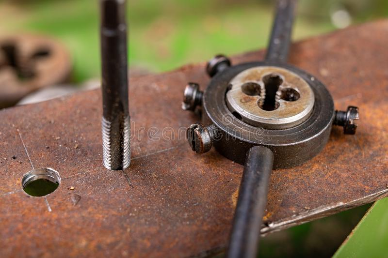 Manual thread cutting in metal. Locksmith accessories for small work in the home workshop. Dark background clamp construction die dies dirty engineering stock image