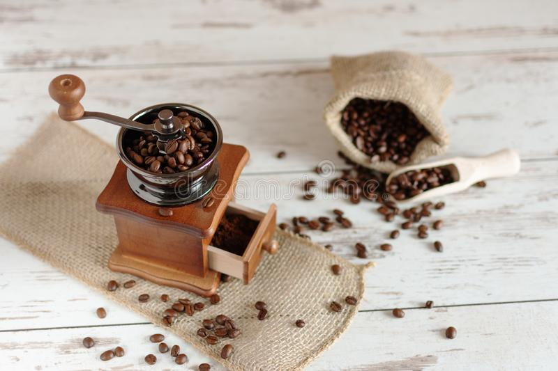 Manual vintage coffee grinder and coffee beans in a burlap bag on a wooden table royalty free stock image