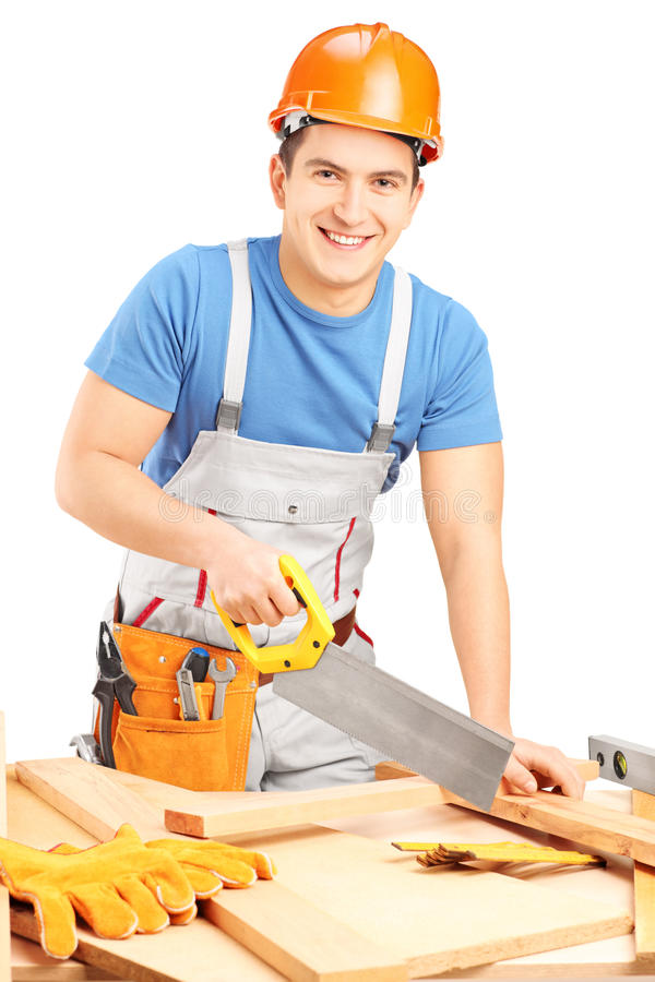 Manual worker with helmet cutting wooden batten with a saw stock photo
