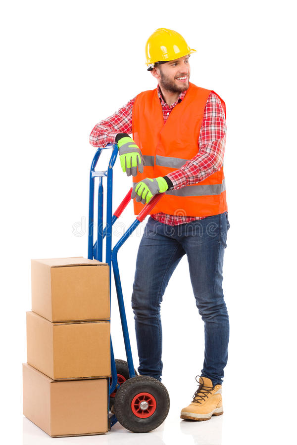 Manual worker and a push cart. Smiling man in yellow hardhat and orange reflective vest posing with a delivery cart and looking away. Full length studio shot royalty free stock photo
