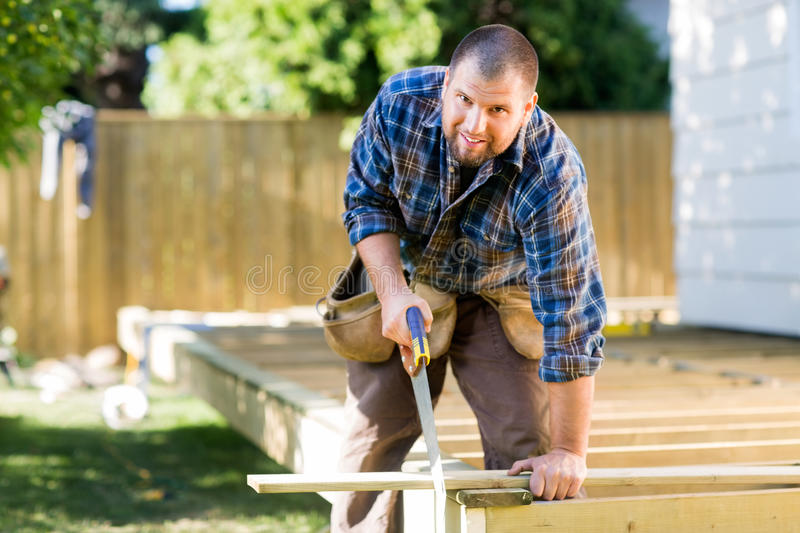 Manual Worker Sawing Wood At Construction Site stock photo