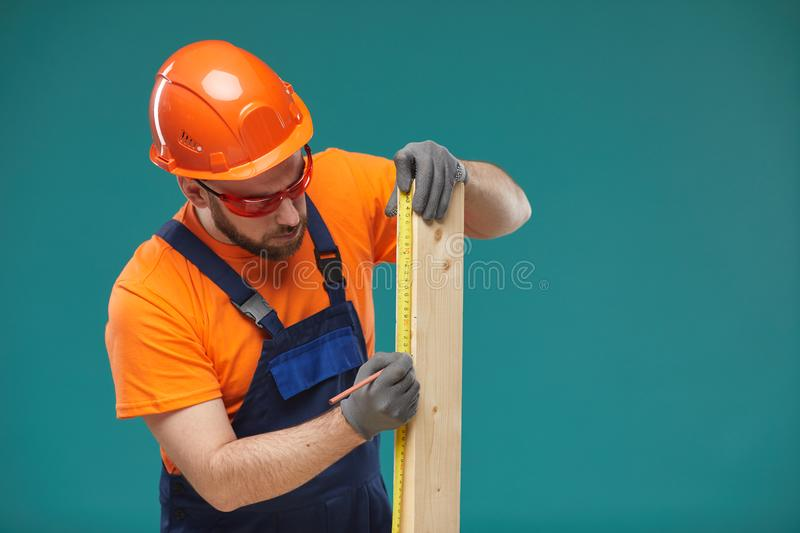 Manual Worker Sizing Wooden Plank royalty free stock images