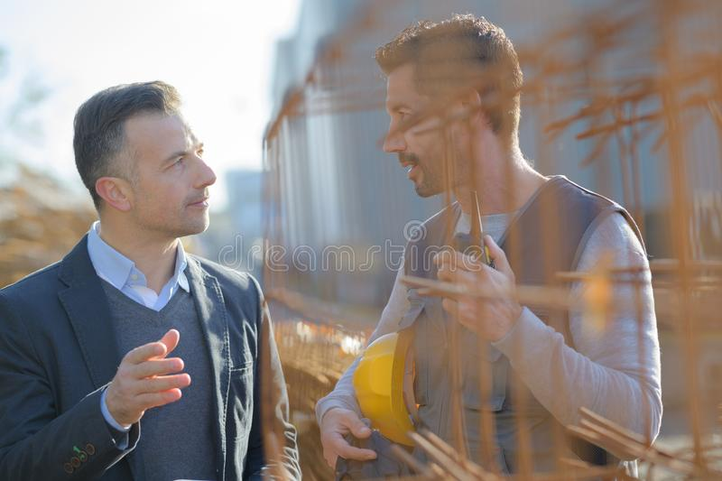 Manual worker talking to manager by rebars stock image