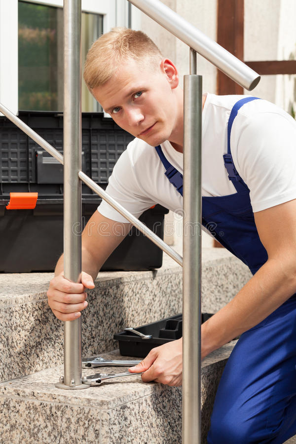 Manual worker tightening stairs banisters royalty free stock images