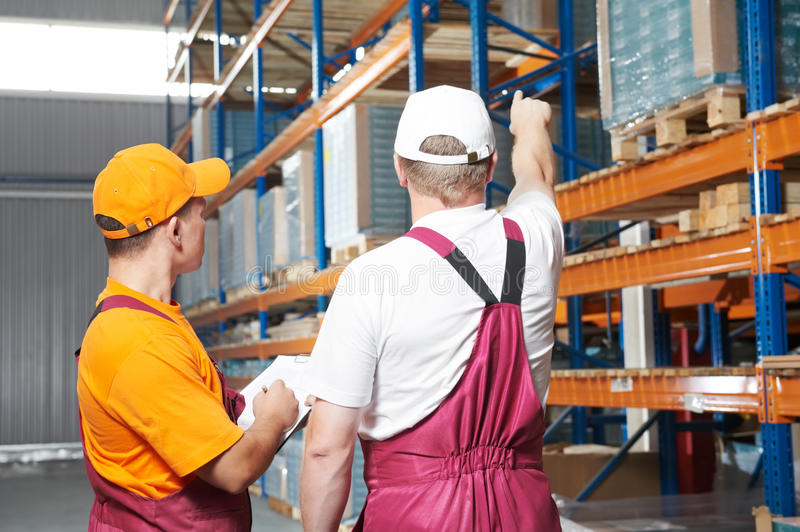 Manual workers in warehouse. Two young workers man in uniform in front of warehouse rack arrangement stillages stock images