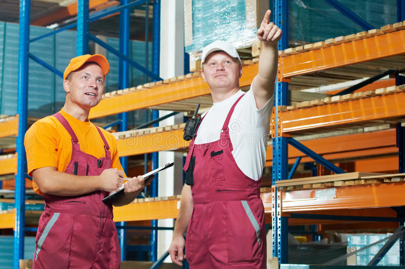 Manual workers in warehouse. Two young workers men in uniform in front of warehouse rack arrangement stillages stock photos