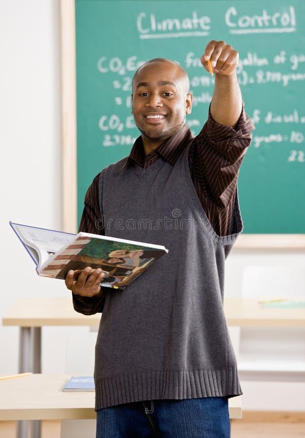 Manuale della holding dell'insegnante che indica l'allievo fotografia stock libera da diritti