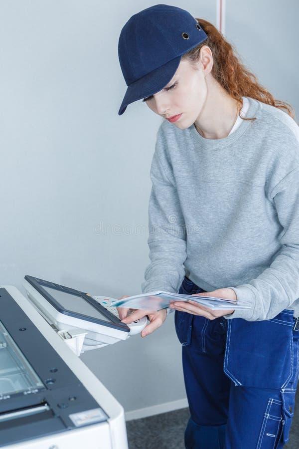 Manuale femminile della tenuta del tecnico e fotocopiatrice di programmazione fotografie stock libere da diritti
