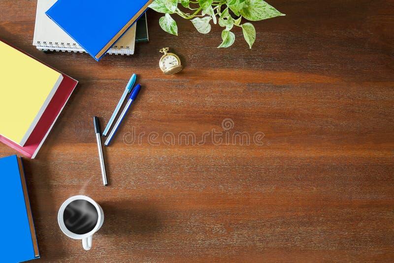 Manuali sudici, taccuini, documenti, penne, pianta verde, orologio da tasca e tazza di caffè macchiato calda sul fondo di legno d fotografia stock