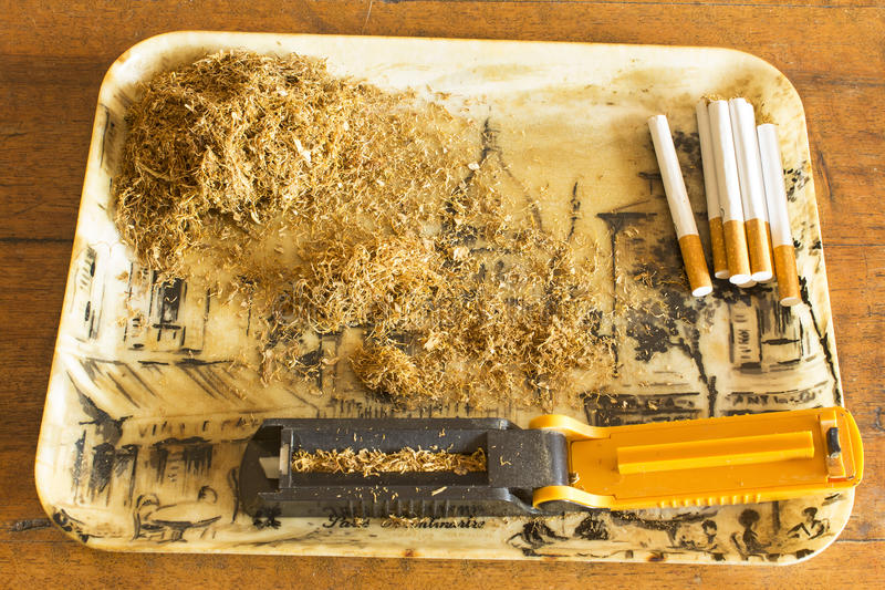 Manually making cigarettes with the tobacco machine.  stock images