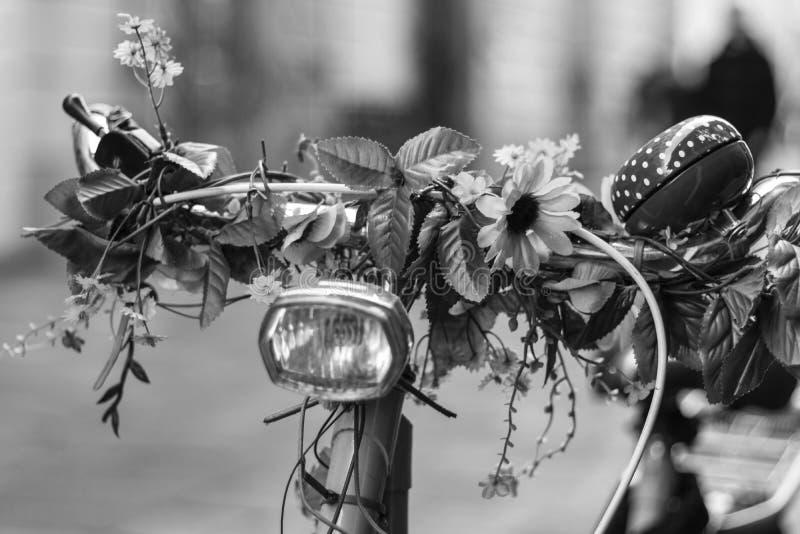 Manubrio della bicicletta con la decorazione floreale, in bianco e nero immagine stock