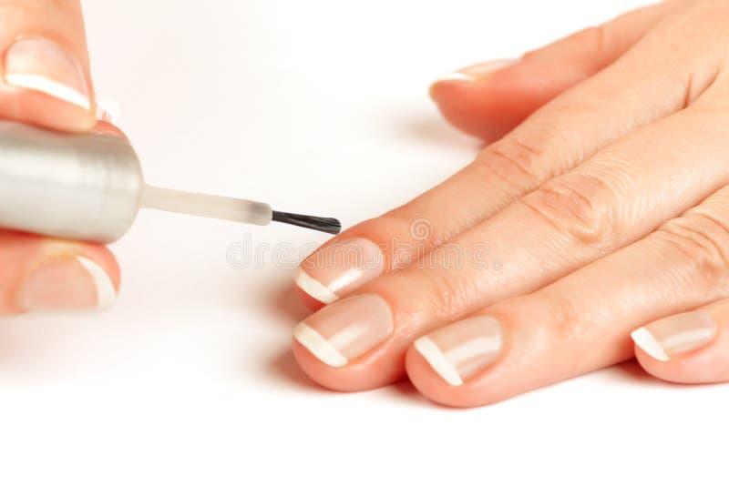 Manucure appliquant le vernis à ongles de regard normal photo libre de droits