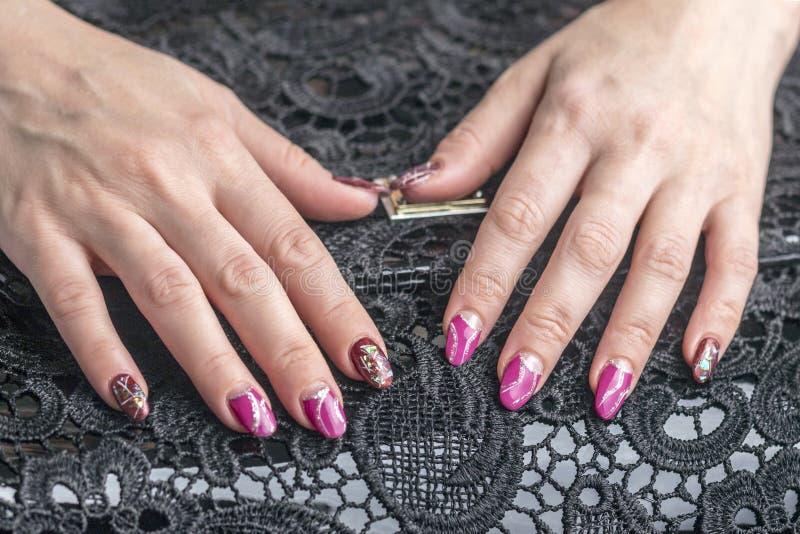Manucure artistique Les mains femelles sont sur un sac noir avec la dentelle photographie stock