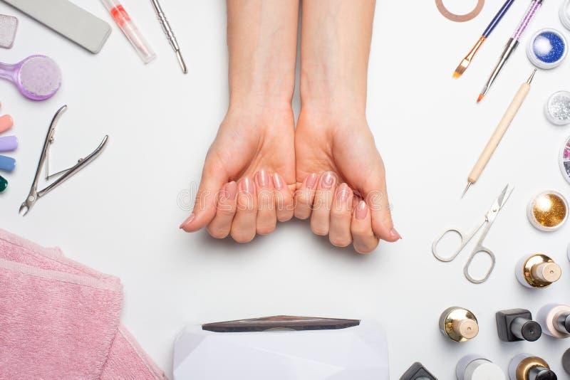 Manucure - beaux ongles avec le vernis à ongles rose images libres de droits