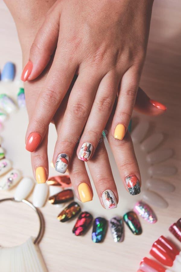 Manucure colorée sur la main femelle images libres de droits