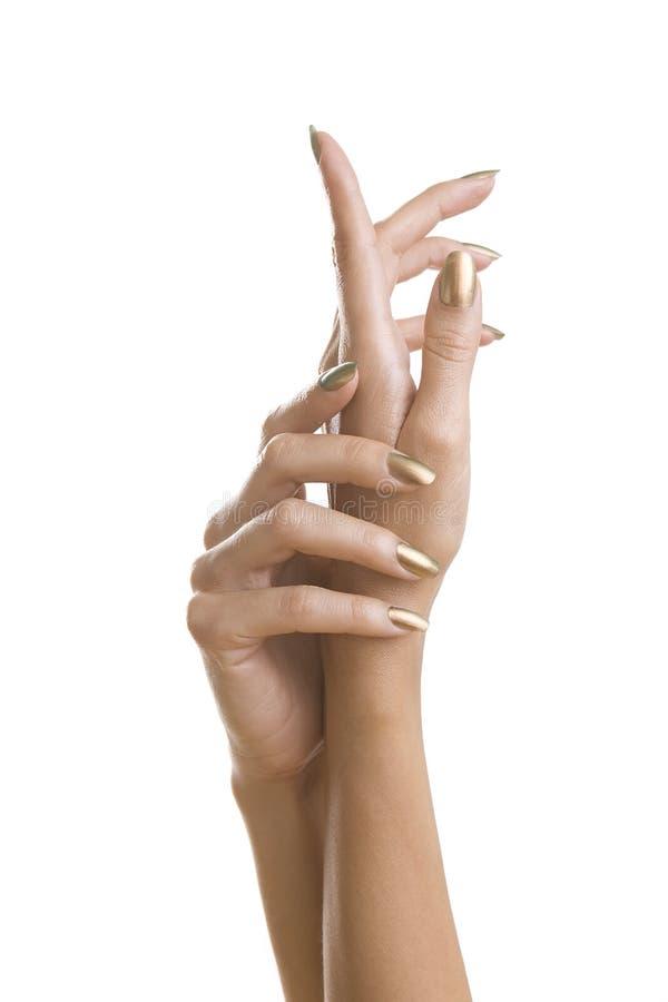 Manucure d'or, mains femelles avec le vernis à ongles d'or brillant photo libre de droits