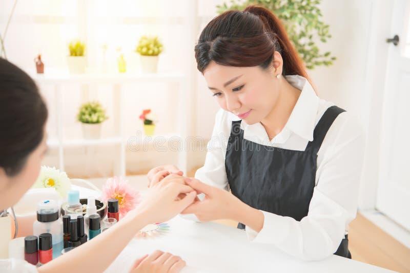 Manucure de femmes vérifiant le soin d'ongle photographie stock libre de droits