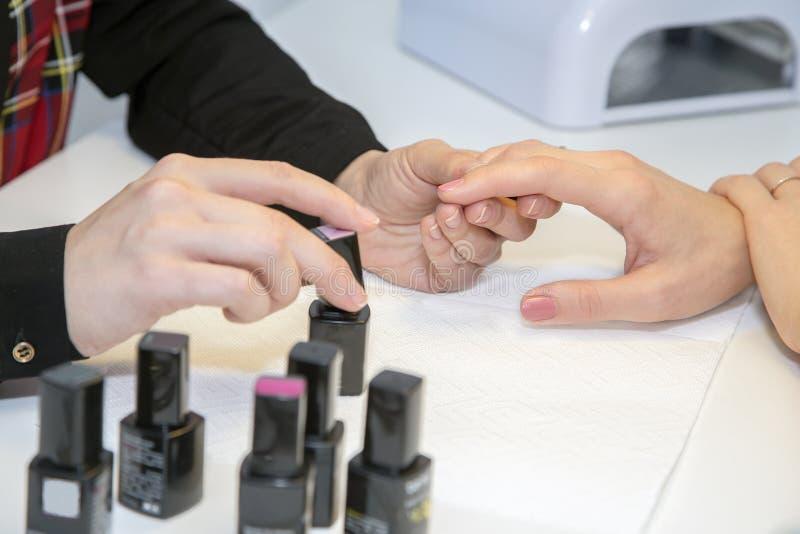 Manucure faisant des ongles de peinture de client de manucure avec le poli image libre de droits
