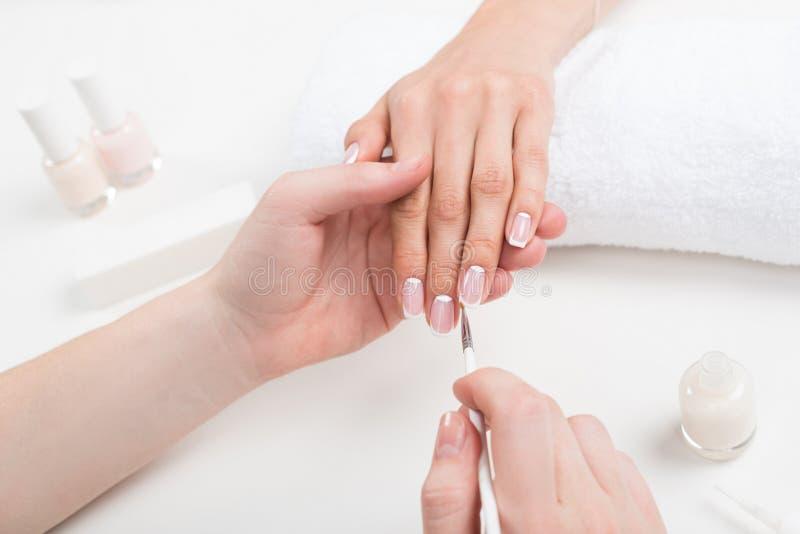 Manucure faisant la manucure à la jeune femme dans le salon de beauté photo libre de droits
