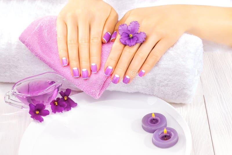 Manucure française avec les fleurs violettes Station thermale photo stock