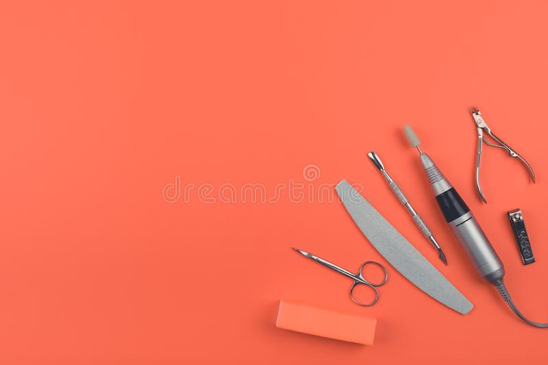 Manucure hybride de matériel, ensemble de soin d'ongle sur le fond de corail Stylo électrique de perceuse de clou, dossier, tampo image libre de droits