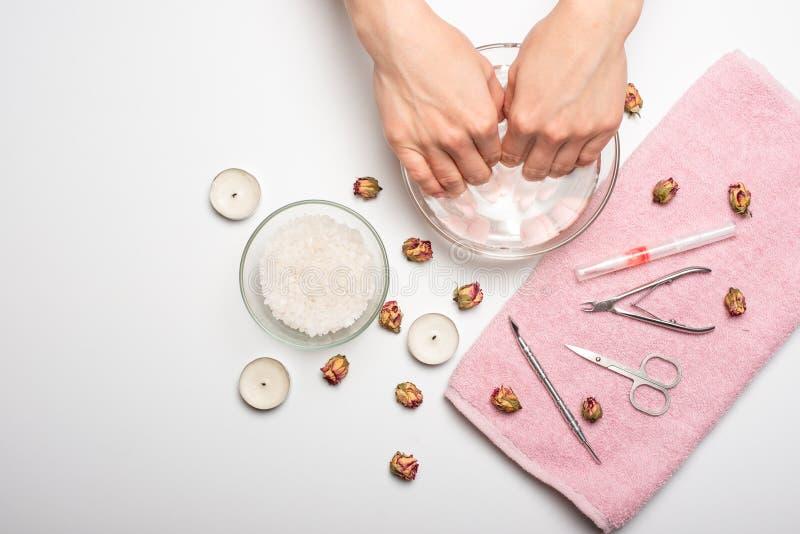 Manucure - la fille elle-même fait, observant les ongles à l'aide d'un outil sur un fond blanc Concept des salons de beauté et de photos stock