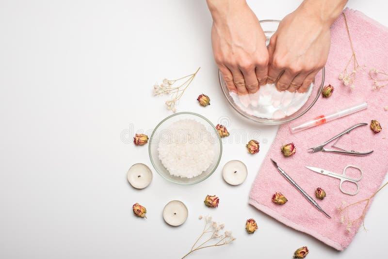 Manucure - la fille elle-même fait, observant les ongles à l'aide d'un outil sur un fond blanc Concept des salons de beauté et de photographie stock libre de droits