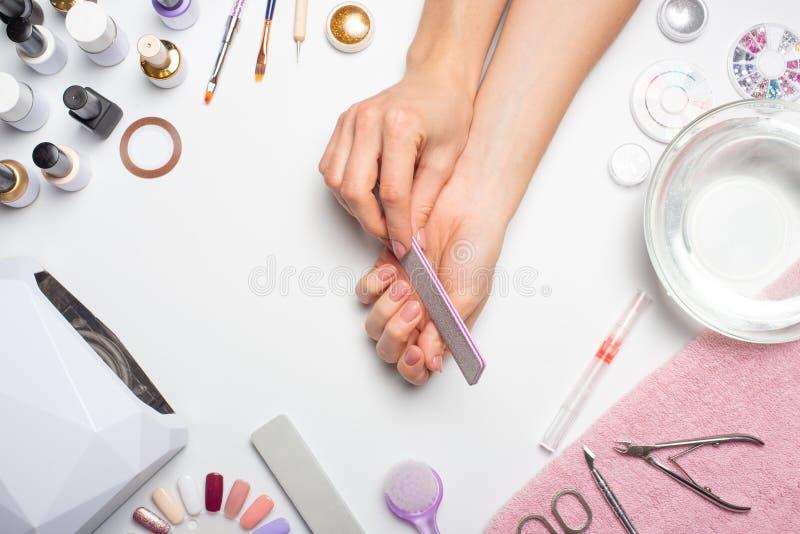 Manucure - la fille elle-même fait, observant les ongles à l'aide d'un outil sur un fond blanc Concept des salons de beauté et de image libre de droits