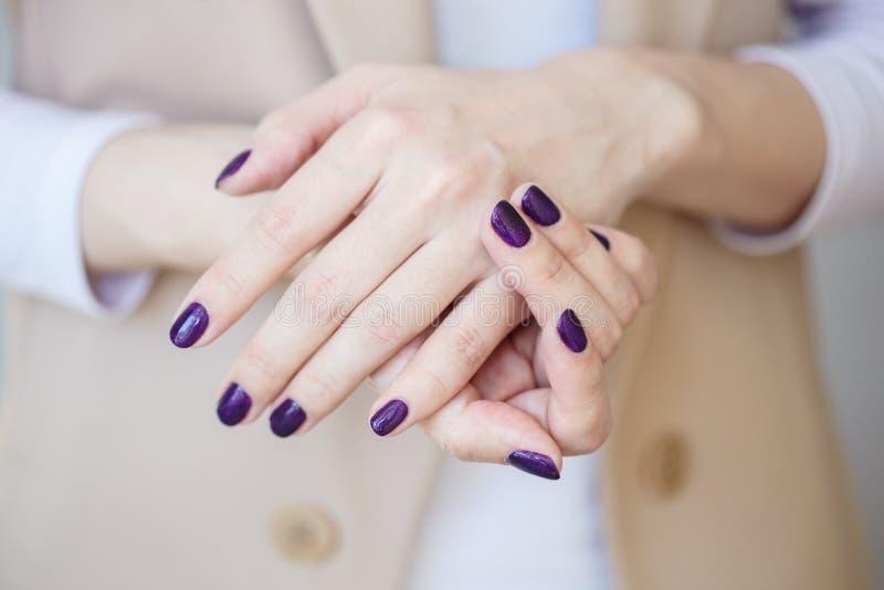 Manucure magnifique, vernis à ongles foncé de couleur d'offre de pourpre, photo de plan rapproché La femelle remet le fond simple photographie stock libre de droits