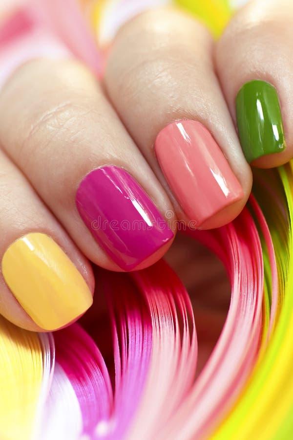 Manucure multicolore avec le vernis à ongles rose, vert, jaune et de pêche images stock