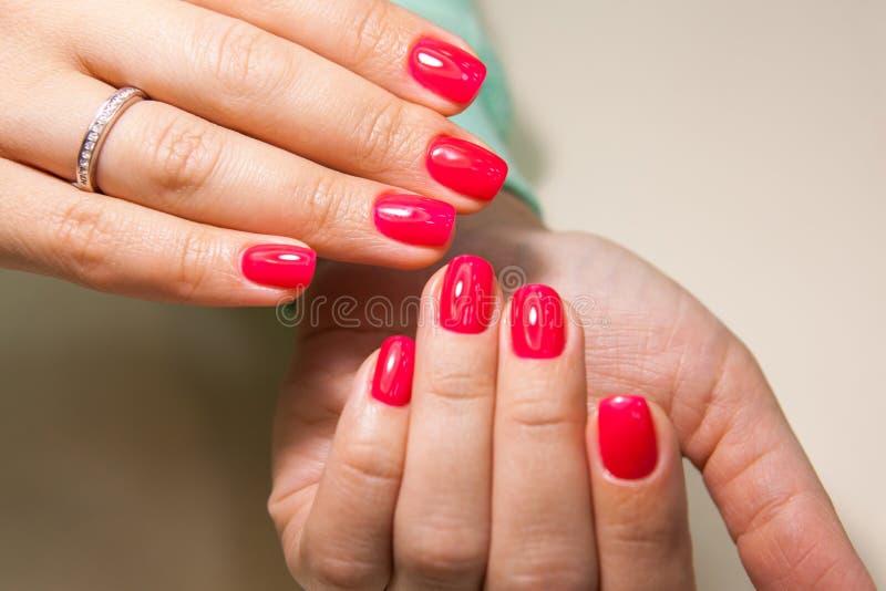 Manucure - photo de traitement de beauté des ongles manicured intéressants de femme avec le vernis à ongles rouge image libre de droits