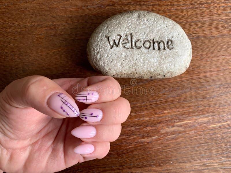 Manucure rose avec avec le modèle géométrique noir sur les ongles en forme d'amande sur un fond brun Accueil d'inscription image libre de droits