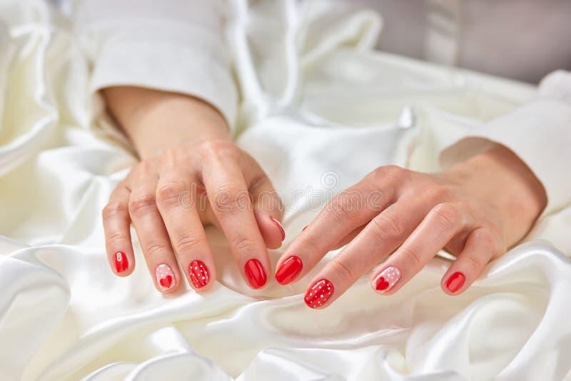 Manucure rouge femelle et soie blanche photos stock