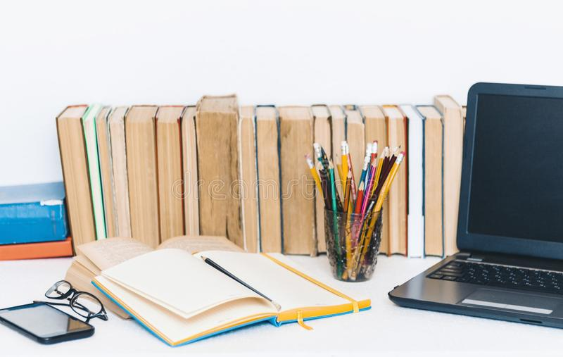 Manuel ouvert, carnet, smartphone, ordinateur portable, pile d'éducation de livres de nouveau au fond d'école, verres et crayons  photo stock