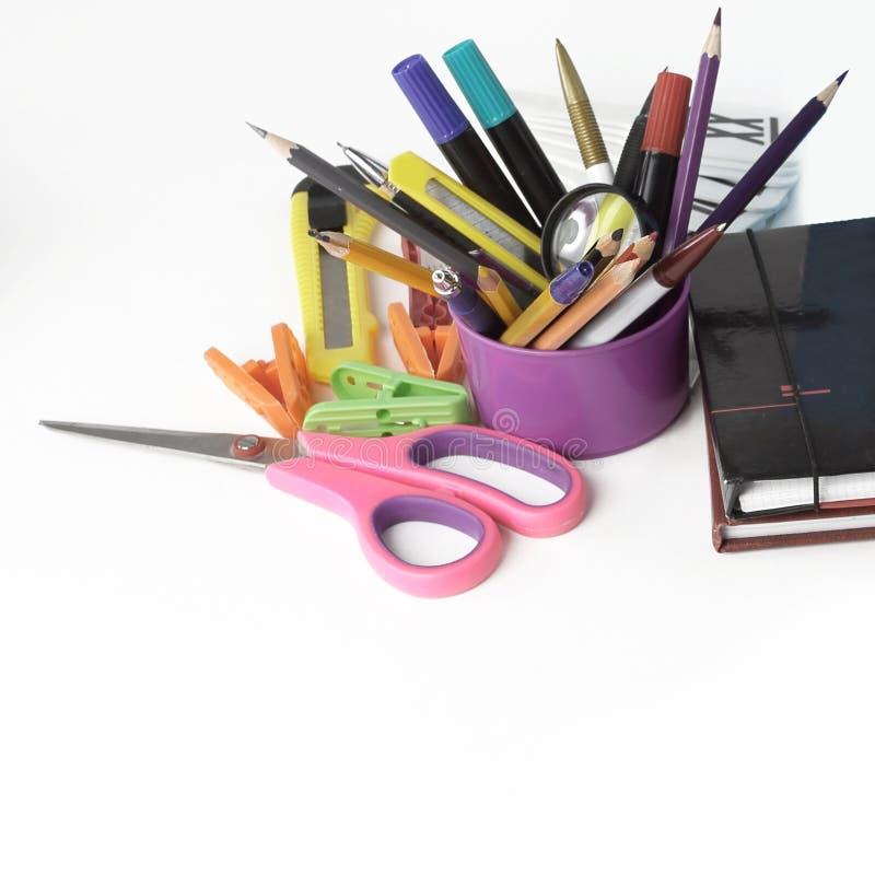 Manuel, stylo et fournitures scolaires sur le fond blanc photos stock