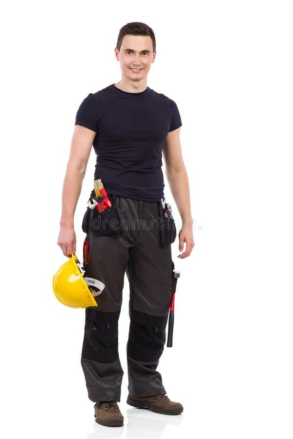 Manuell arbetare som poserar och rymmer den gula hardhaten arkivfoto