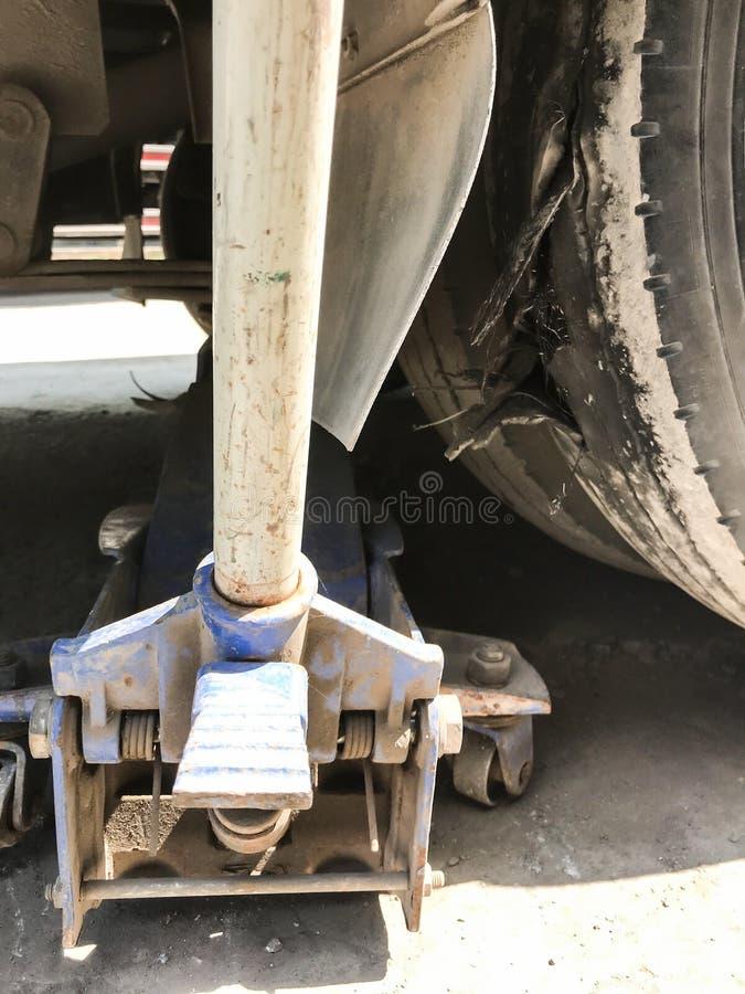 Manuell mekanisk stålarelevator som silar upp en bil för att ändra bristningsgummihjulet i ett garage fotografering för bildbyråer