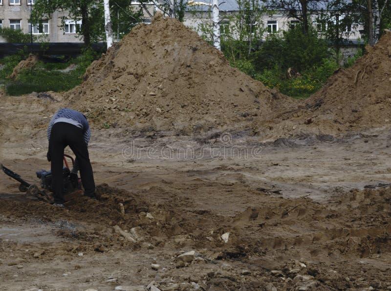 Manuelle Eisbahn Straßenarbeitskraft preßt die Erde auf dem Weg zusammen Legen des Asphalts stockfotografie