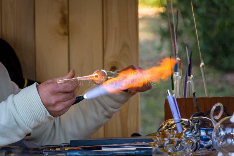Manuelle Herstellung von Glaswaren mit Gasbrenner stockbilder