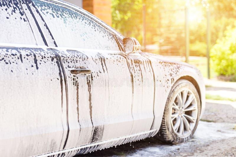 Manuelle Waschanlage Waschendes Luxusfahrzeug mit weißem schäumendem Reinigungsmittel Automobilreinigungsselbstservice stockfotografie