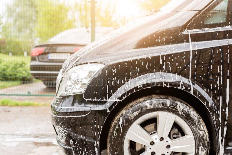 Manuelle Waschanlage Waschendes Luxusfahrzeug mit weißem schäumendem Reinigungsmittel Automobilreinigungsselbstservice stockfotos