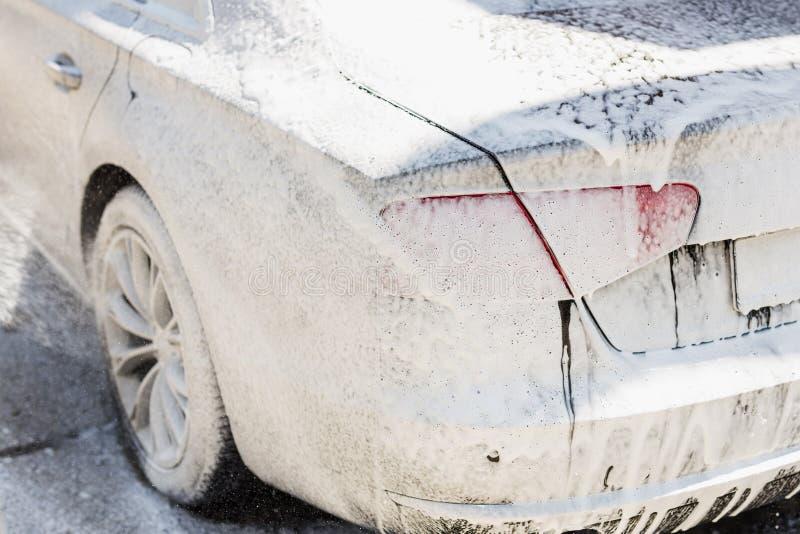 Manuelle Waschanlage Waschendes Luxusfahrzeug mit weißem schäumendem Reinigungsmittel Automobilreinigungsselbstservice lizenzfreie stockbilder