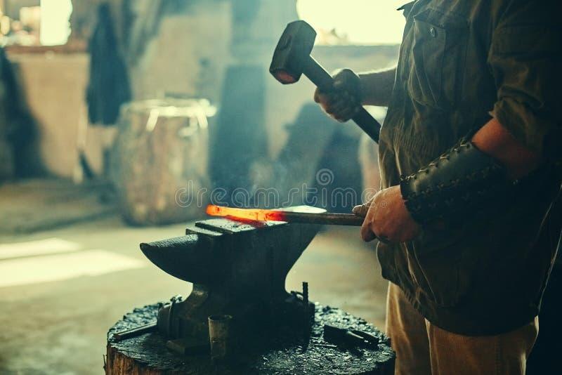Manuellt arbete av en svart smed i en svarta shop Hammer blåser på järnfakturan på städet Att glömma svärdblad är en retro royaltyfri foto