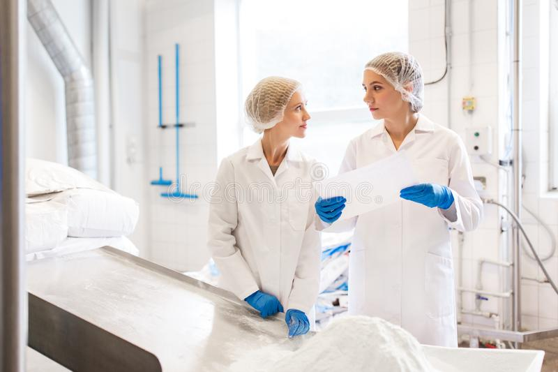 Women technologists working at ice cream factory royalty free stock photo
