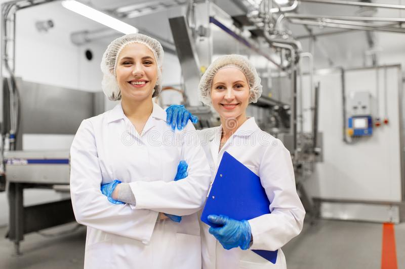 Happy women technologists at ice cream factory royalty free stock photos