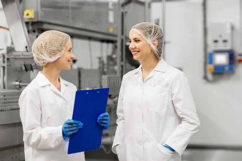 Happy women technologists at ice cream factory stock photos