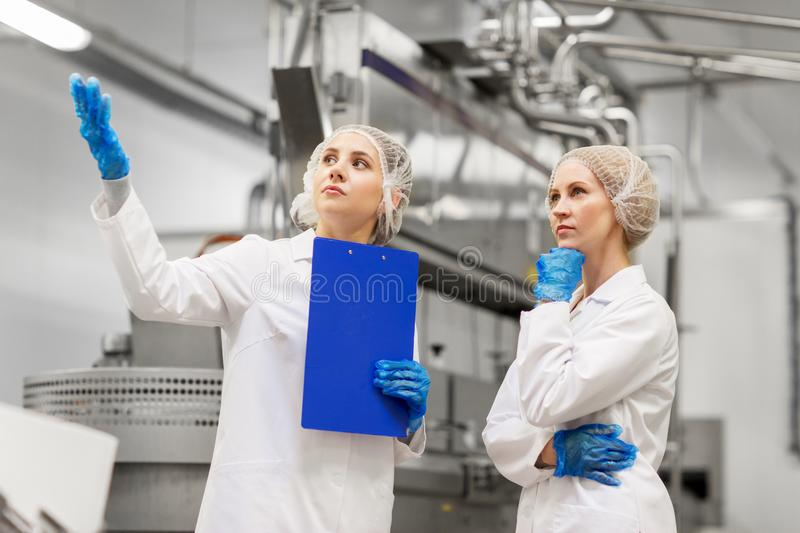 Women technologists at ice cream factory royalty free stock photography